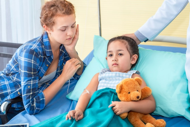 Pediatra (médico), madre tranquilizadora y discutiendo sobre su hija. chica paciente triste en el dormitorio del hospital.