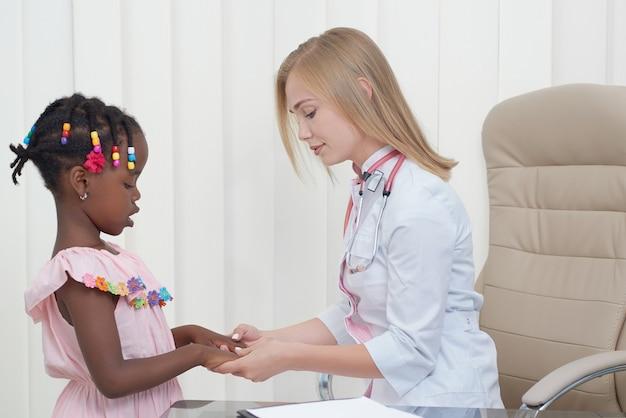 Pediatra de mujer, inspeccionando a la niña afro en el gabinete.
