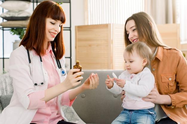 Pediatra que da una dosis de una cucharada de medicamento líquido para beber jarabe a un paciente bebé