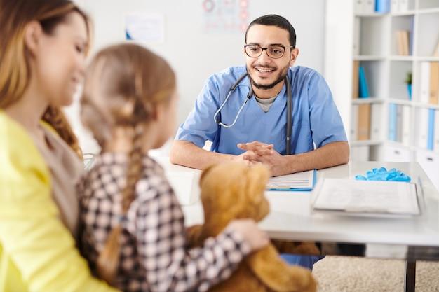 Pediatra sonriente hablando con el niño