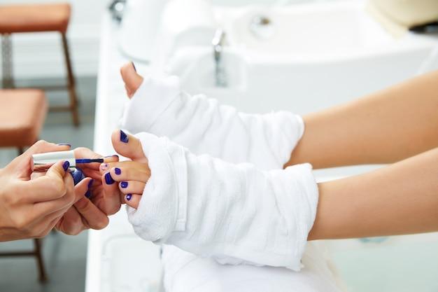 Pedicura uñas esmalte azul en salon de uñas.