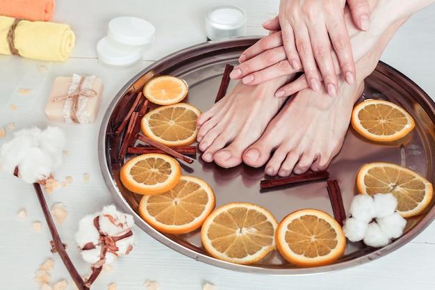 Pedicura y manicura en el salón de spa con rodajas de naranja, canela y algodón sobre una mesa de madera blanca