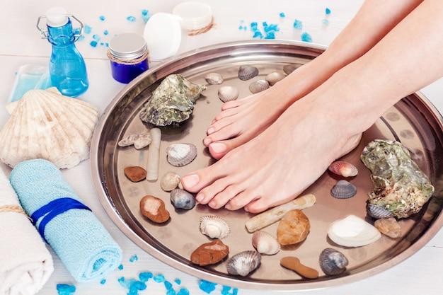 Pedicura en el salón de spa con conchas y piedras sobre una mesa de madera blanca