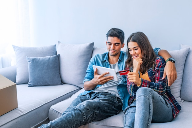 Pedido en línea. pareja haciendo llamadas a la entrega de alimentos mientras está sentado en el sofá en el nuevo apartamento