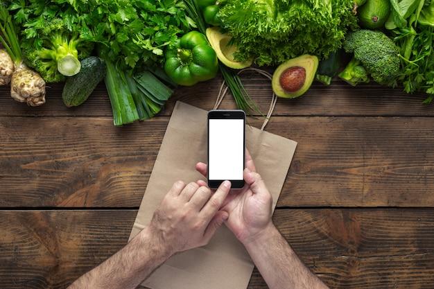 Pedir comida en línea el hombre tiene un teléfono inteligente con pantalla en blanco en una mesa de madera con vegetales verdes frescos