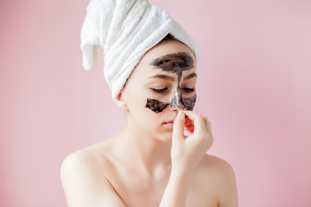 Peeling cosmético de belleza. closeup hermosa mujer joven con máscara de pelar negro en la piel
