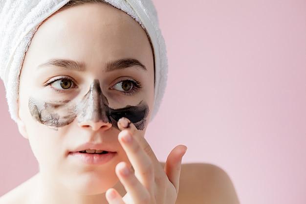 Peeling cosmético de belleza. closeup hermosa mujer joven con negro pelar la máscara en la piel.