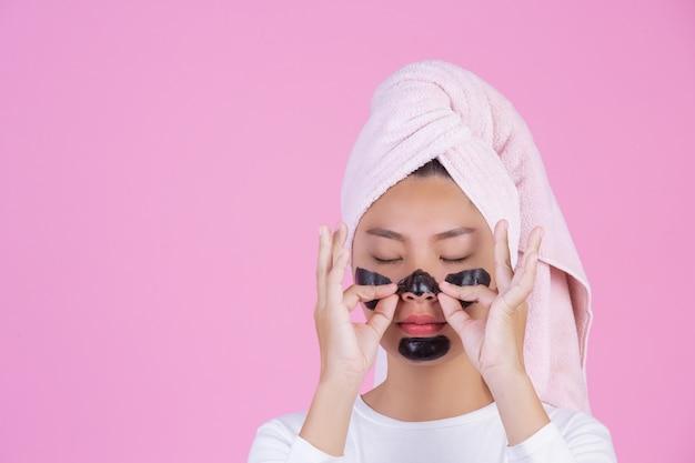Peeling cosmético de belleza. hembra joven con máscara de peeling negro en la piel cosmética producto de peeling para el cuidado de la piel en la cara en un rosa.