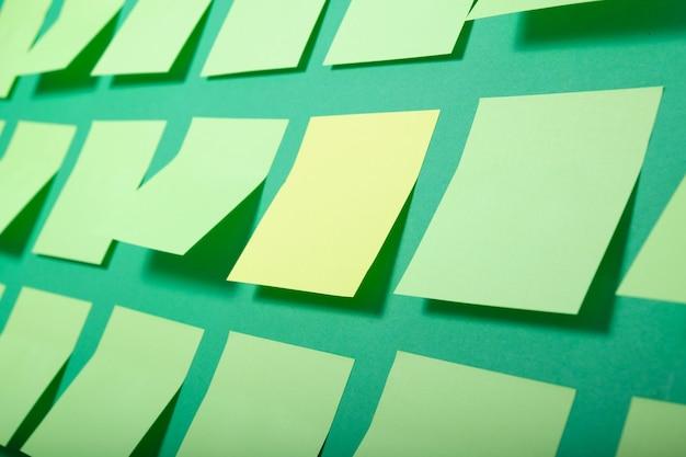 Una pegatina amarilla y muchas notas adhesivas de color verde claro sobre un fondo verde