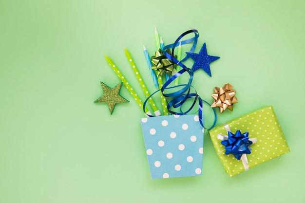 Pegatina de estrellas; velas; cinta; caja de regalo y arco sobre fondo verde