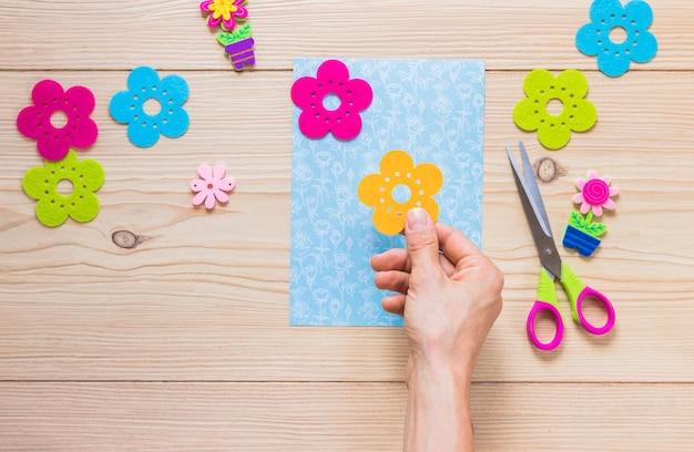 Pegatina de flor de una persona pegado a la mano en papel de bloc de notas