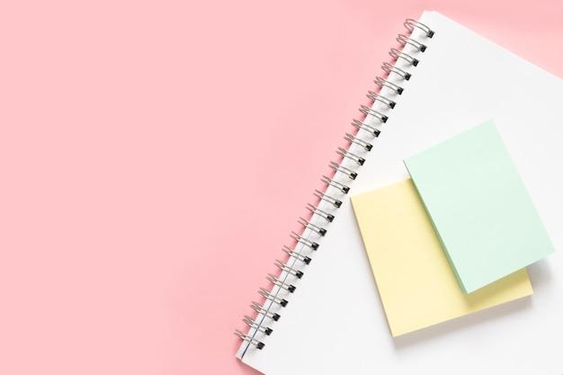 Pegatinas amarillas y verdes se encuentran en un cuaderno blanco.