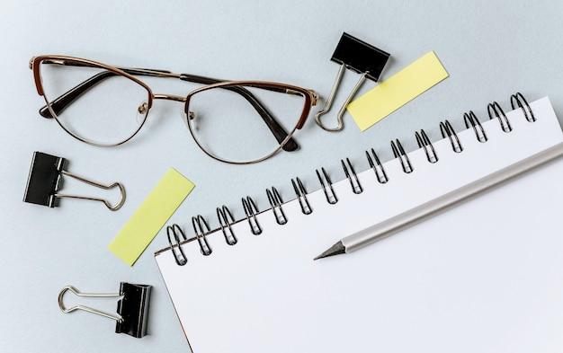 Pegatinas en blanco, lápices, gafas, cuaderno, clips de carpeta y chinchetas aisladas sobre fondo blanco y azul