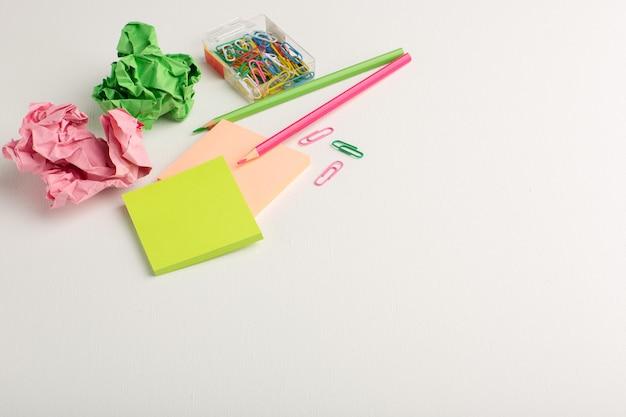 Pegatinas de colores de vista frontal con lápices sobre superficie blanca