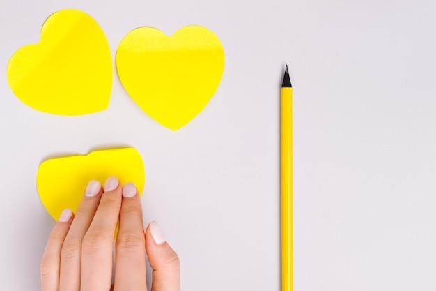 Pegatinas luminosas en forma de corazón, lápiz y espacio en blanco para publicidad sobre un fondo gris definitivo.