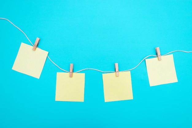 Pegatinas de papel en blanco cuelgan de una cuerda con pinzas de madera. copie el espacio para notas