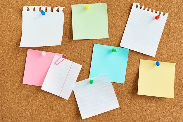 Pegatinas de papel de colores sobre un fondo de tablero de corcho