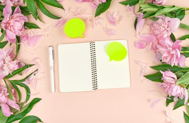 Pegatinas de papel vacías y cuaderno abierto sobre flores de durazno.