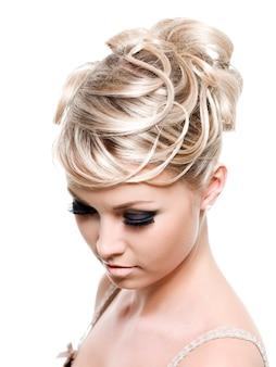 Peinado de moda creativa en el cabello rubio largo femenino