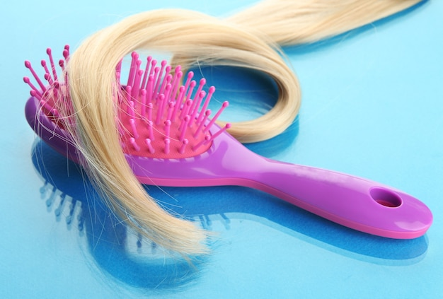 Peine cepillo con pelo, sobre superficie azul