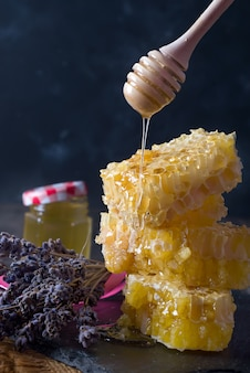 Peine de miel con flores de lavanda - comida dulce sobre fondo oscuro