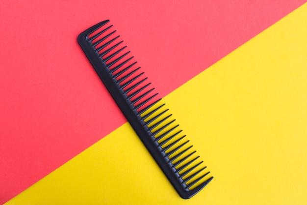 Peine de pelo negro en el centro de la superficie bicolor. vista superior. copia espacio