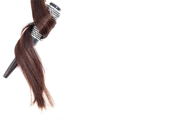 Peine con el pelo oscuro aislado en la vista superior del fondo blanco