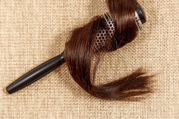 Peine con el pelo oscuro en una vista superior de fondo beige