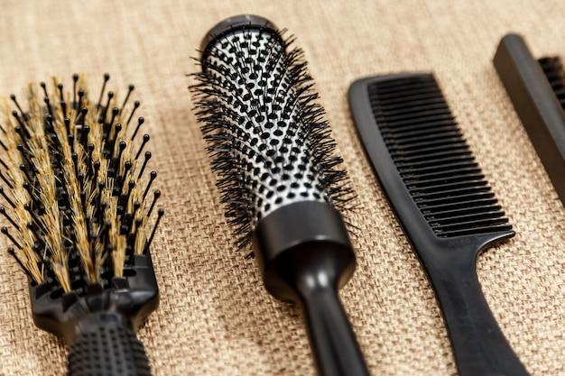 Peines y herramientas de peluquería sobre fondo beige.