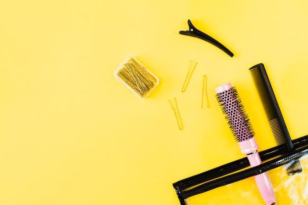 Peines y horquillas cerca de bolsa de cosméticos