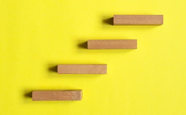 Peldaños de madera o escaleras sobre superficie amarilla. camino al concepto de éxito y desarrollo.