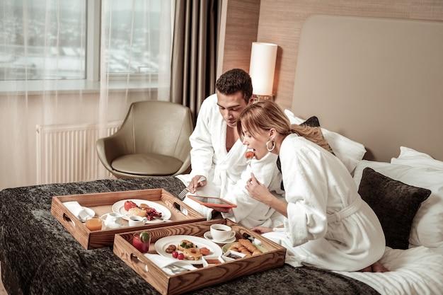 Película en tableta. pareja comiendo un delicioso desayuno en la cama y viendo una película interesante en tableta