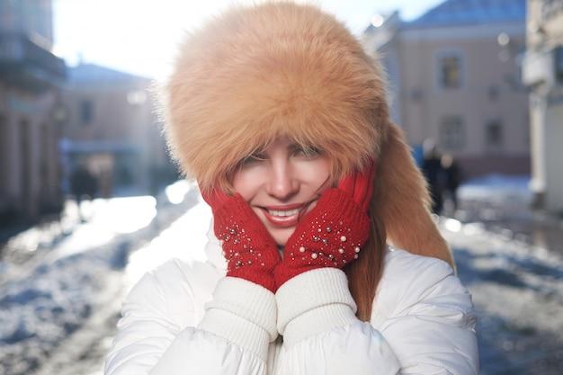 Pelirroja blanca flaca, vestida con sombrero de piel de zorro, lindo retrato de invierno.