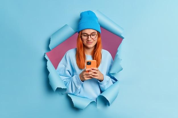 Pelirroja complacida joven mujer caucásica utiliza tipos de teléfonos móviles mensajes sms navega en las redes sociales lleva sombrero azul y sudadera.