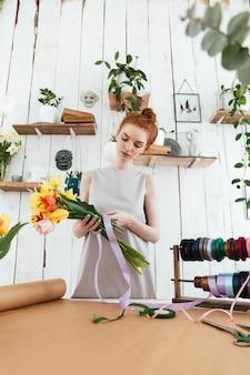 Pelirroja dama floristería recogiendo ramo mientras está de pie cerca de la mesa
