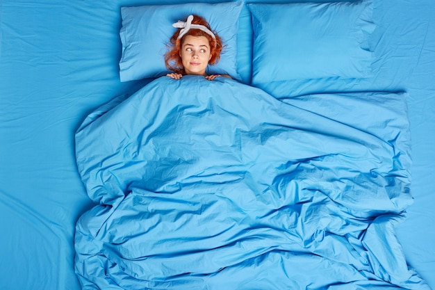 Pelirroja joven mujer europea acostada debajo de una manta suave usa diadema duerme en un dormitorio acogedor disfruta de los buenos días se siente cómodo usa diadema mira pensativamente a un lado los planes del día