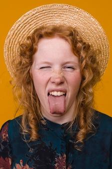 Pelirroja joven mujer pecosa mostrando lengua