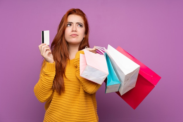Pelirroja joven sosteniendo bolsas de compra y una tarjeta de crédito y pensando