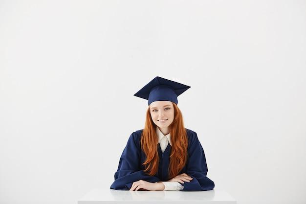 Pelirroja mujer graduada sonriendo.