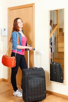 Pelirroja mujer positiva en jeans con equipaje salir de la casa
