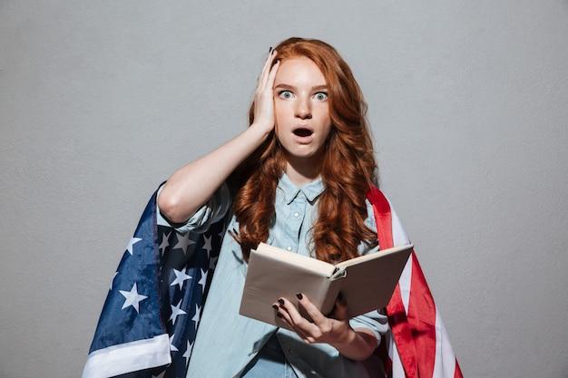 Pelirroja sorprendida joven leyendo el libro con la bandera de estados unidos