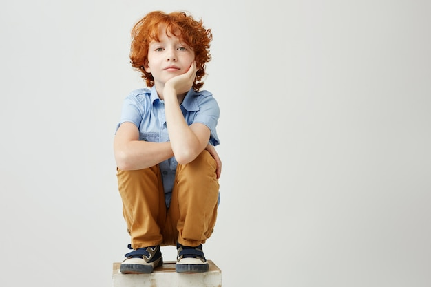 Pelirrojo divertido niño sentado en la caja, sosteniendo la cabeza con la mano