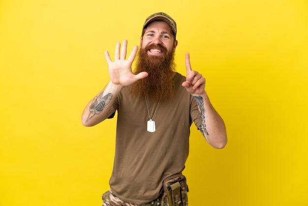 Pelirrojo militar con placa de identificación aislado sobre fondo amarillo contando seis con los dedos