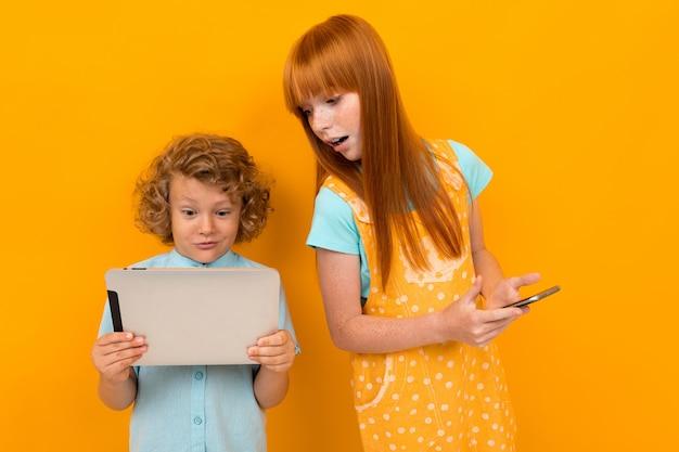 Pelirrojo sorprendido niño y niña con un teléfono y una tableta sobre un fondo amarillo brillante