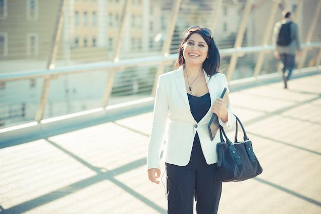 Pelo largo y negro elegante mujer de negocios elegante con tableta