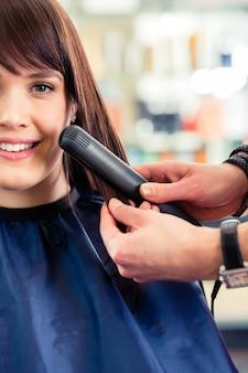 Pelo de mujer vestido de coiffeur masculino con plancha en tienda
