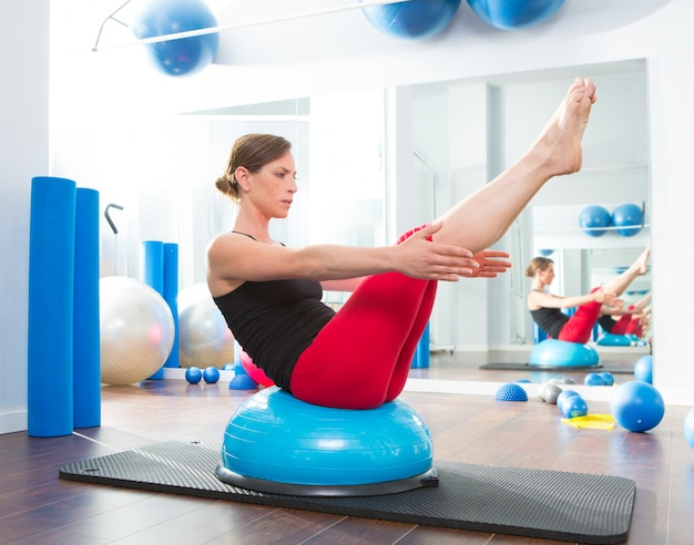 Pelota bosu para instructor de fitness mujer en aeróbic.