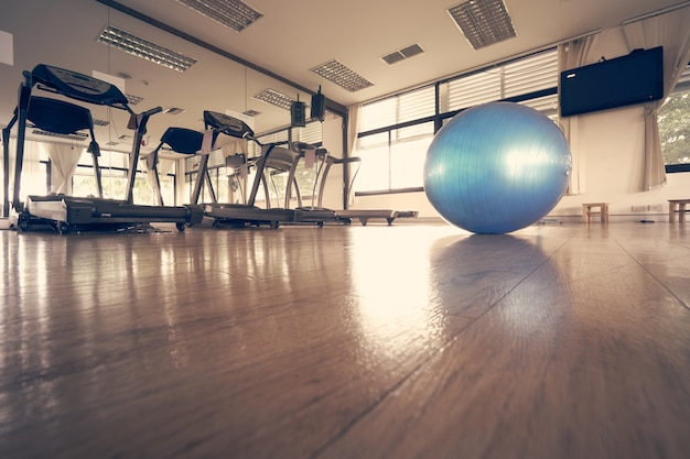 La pelota de ejercicio azul colocada en el centro de la sala de fitness