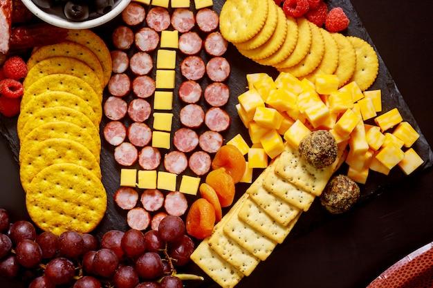 Pelota de fútbol hecha de queso y salchichas para tablero de charcutería. concepto de juego de fútbol americano.