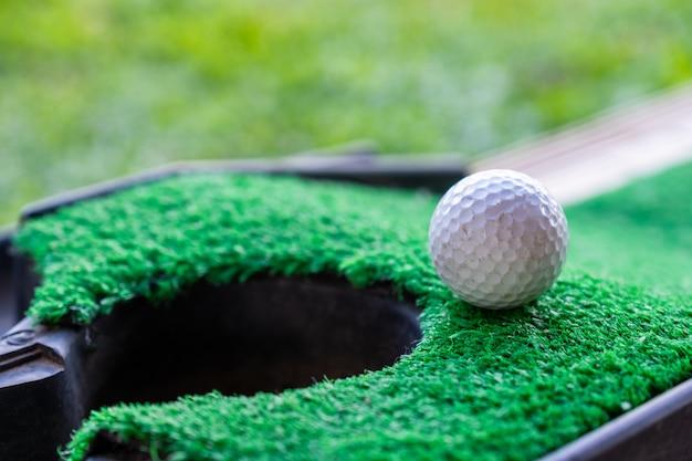 Pelota de golf borde agujero taza en césped